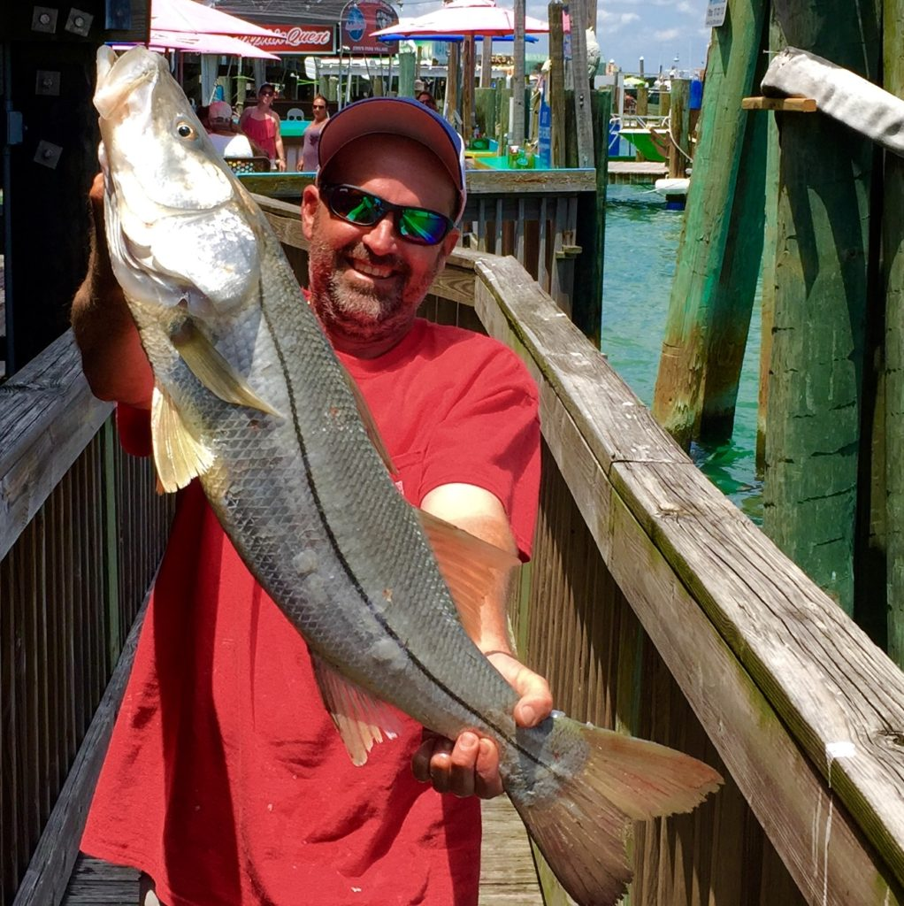 Jacob 'Smokey' Grant showing off a monster snook he caught while handling a pigfish under the dock at Hubbard's Marina