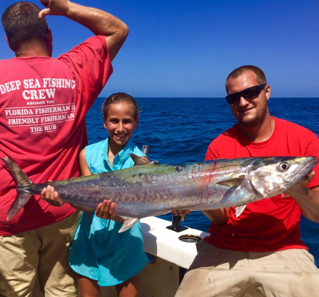 Left-Right- Paul Early, Mia Rosace from st. pete, and Captain Anthony Belmonte showing off a big kingfish from the HUB private charter at Hubbard's Marina